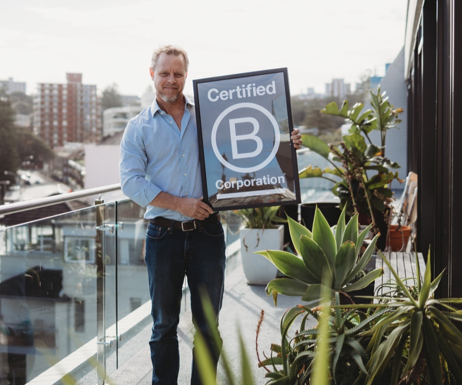 Edge Environment CEO Jonas Bengtsson showing B Corporation Certificate from Manly office
